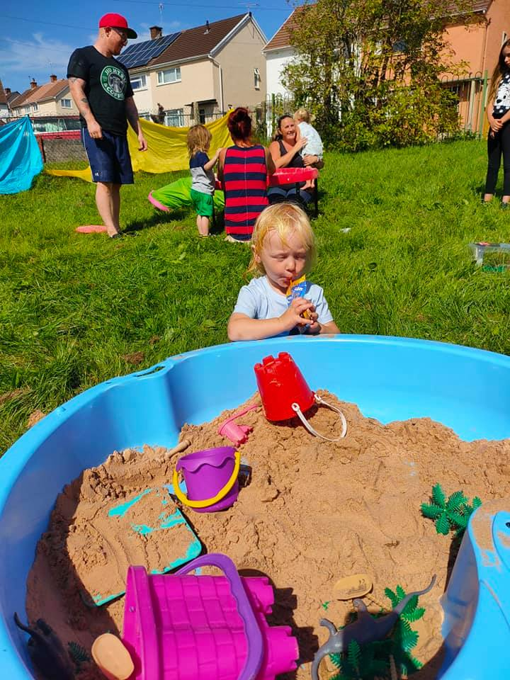 a young boy drinking next to a sand pit full of toys