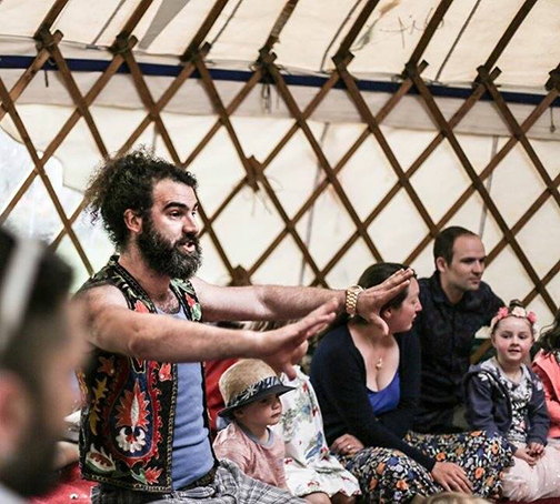 A bearded man with curly hair performs a story to a mixed age audience inside a yurt.