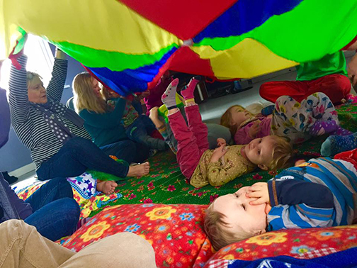 multiple children lie under a multicoloured parachute as adults waft it gently during relaxation time