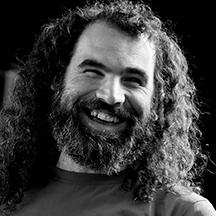 Dave Morris of KeyCreate in black and white with a full beard, curly hair and a beaming smile