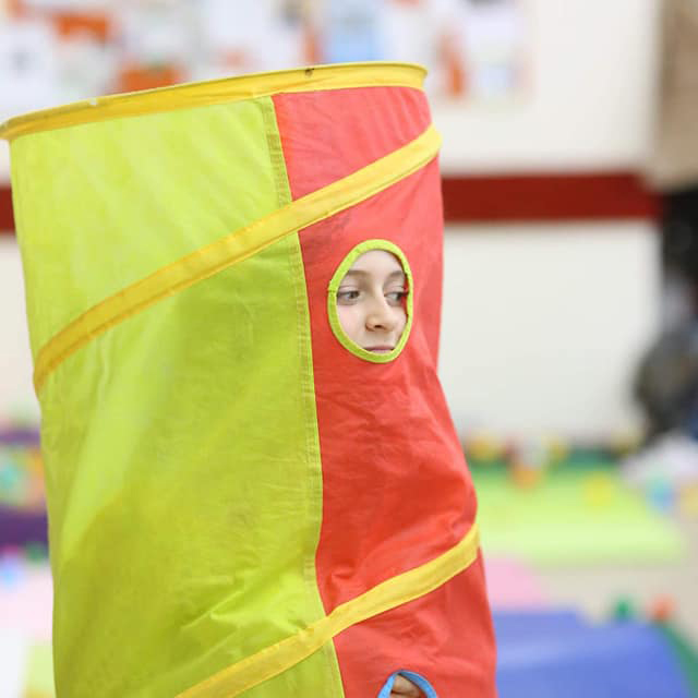 A young girl peeks out of a spy hole in a yellow and red play tunnel.