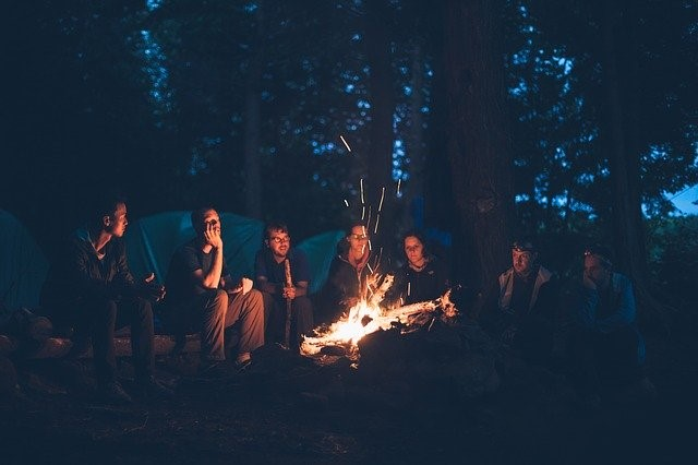 A group sitting by a fire out in the woods while camping.
