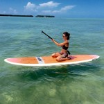 Girl kneeling on a paddlebard, paddling into the Florida Keys