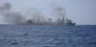 A large body of water with smoke coming out of it - Guided missile destroyer