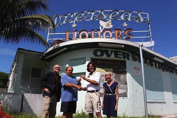 Robert M. Parker, Jr. et al. posing in front of a building - Overseas Pub and Grill