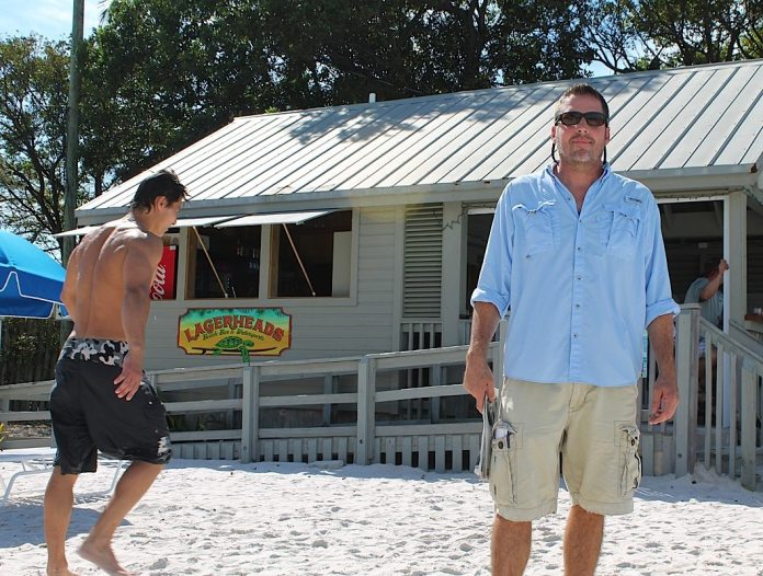 Lagerhead's Beach Bar & Watersports General Manager Patrick Godsell poses on the busy, white sand beach sandwiched between two resorts.