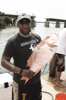 A veteran hoists a red snapper caught while fishing near Pigeon Key.