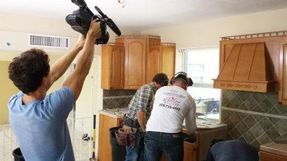 A cameraman films TV host Matt Blashaw, left, and a Royal Crest Construction worker, right, as they dismantle the existing kitchen.