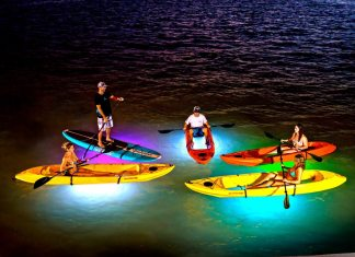 See underwater after dark - A group of people standing next to a body of water - Light