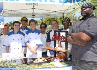 18th Annual Taste of the Islands pleases taste buds - A group of people standing around a table - Chef