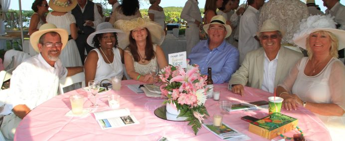 Mark Schoonerover, Rev. Sara Fowler, Bob and Donna Harvey and Craig and Cheryl Cate sit at the big table. The host Ed Knight wasn't available for the party this year.