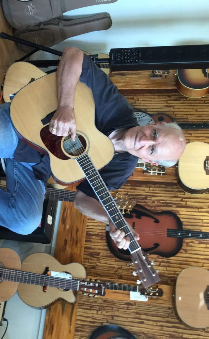 Craftsman retires to build guitars - A person holding a guitar - Acoustic guitar