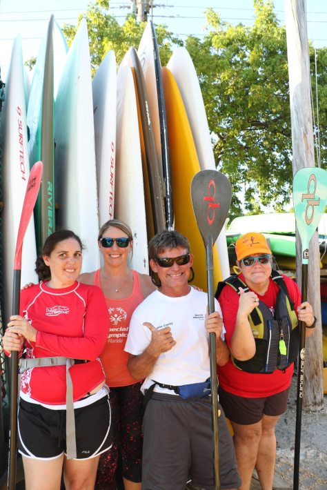 Athletes Jennifer Averette, Scott Hart, and Linnea Edwards stand with Head Coach Liana Pyne-Baron. Hart used to be an athlete, but has progressed to an assistant coach. He also received an award from the Coast Guard for saving Edwards from heat exhaustion and dizziness when he towed her to shore behind a board. 'It's an incredible experience to be a part of this,' Pyne-Baron said.