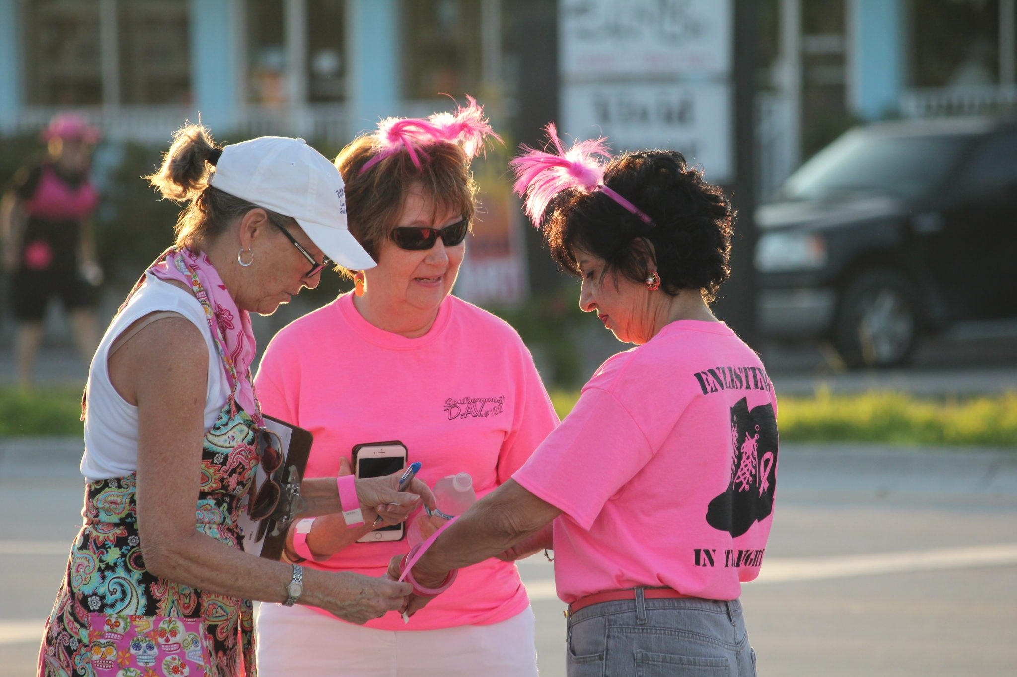 Debbie Hegland, left, and Helen Catchpole, right, and a friend put on their pink bracelets to walk.