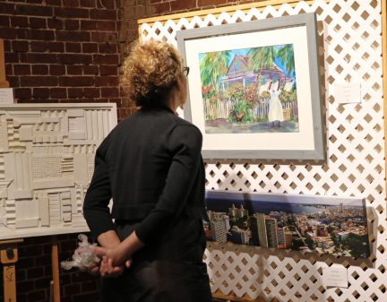 A bidder looks at 'Days Gone By' by Martha dePoo before the bidding starts.