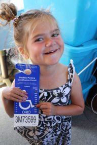 Mia holds up the handicap placard that needs to be renewed. Her mom said when she first saw the 2017 renewal date, she never thought she'd see the day she'd have to renew it. KRISTEN LIVENGOOD/Keys Weekly