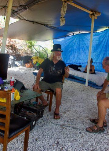 Wisteria Island: It's complicated - A man sitting on a table - Wisteria Island