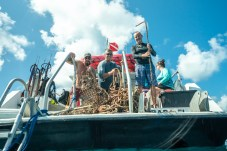 - Eric Billips, John El-Koury and Derke Snodgrass pose with their haul after a successful morning dive on the reef.