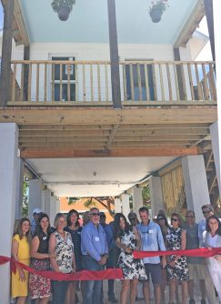 Ribbon cut on first 'Maggie House' - A group of people standing in front of a building - Holly Merrill Raschein