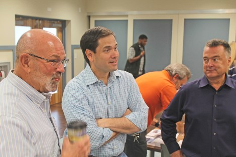 Sen. Marco Rubio, center, chats a little Dolphins football with Mayor David Rice, left, and Village Manager Seth Lawless before the start of the meeting at Marathon City Hall to discuss canal cleanup progress.