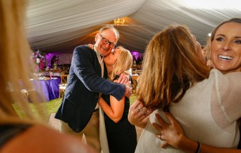 Dr. Alan Percy, a pediatric neurologist specializing in Rett syndrome, is hugged by event cohost Kathryn Kissam, at center, during the second annual Purple Pumpkin Gala at Founders Park. Photo by Doug Finger