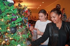 "Maylin Ibarra, left, and Yessenia Crespo sprinkle tinsel on the IOA Insurance Agency tree. It has a clever ""Nightmare before Christmas"" theme."