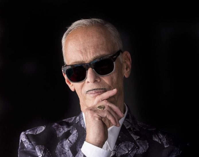 John Waters is Coming to Town… an Interview with the Icon - A man wearing glasses talking on a cell phone - Make Trouble