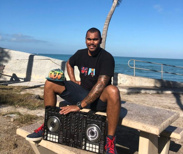 DJ FIJI brings multicultural experiences from global waters - A man sitting on a bench next to a body of water - Florida
