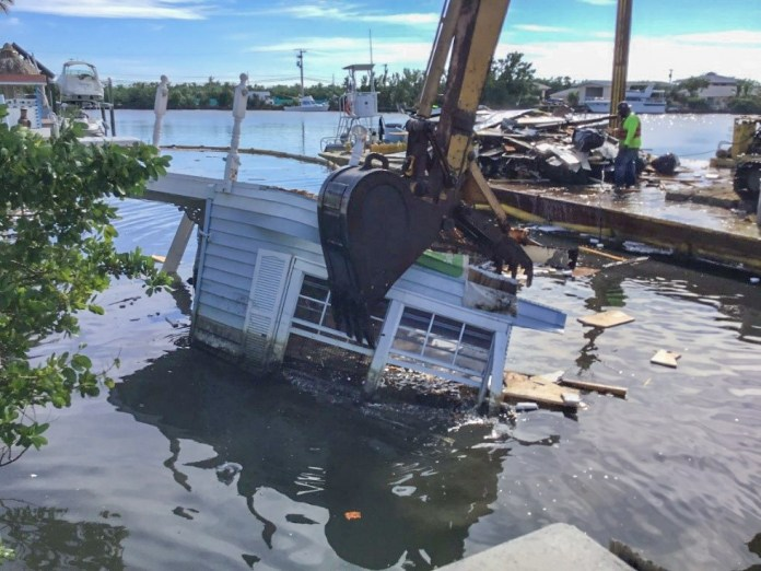 Remains of Irma: Canal Cleanup Nears Completion - A boat is docked next to a body of water - Florida Keys