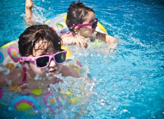 Our Barefoot Doctor Offers Sunscreen Tips for the Kids - A child swimming in a pool of water - Summer camp
