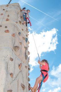 Skye Caballero, top, and Aaliyah Ruiz can see everything from atop the rock climbing wall. They were visiting from Miami.