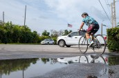 Cyclists go 125 miles to support children's shelter - A man riding a bicycle next to a lake - Road bicycle