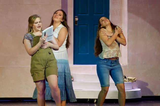 Mamma Mia' comes alive at MHS this weekend - A woman standing in front of a building talking on a cell phone - Mamma Mia!