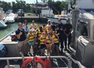 Marathon ladies teach girls about boating safety - A group of people riding on the back of a truck - Boating