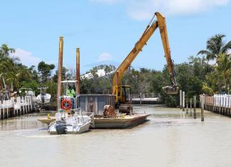 Canal dredging: 2 down, 8 to go - A boat is docked next to a body of water - Canal