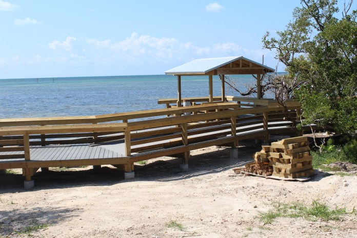 Anne's Beach reopens following damage sustained from Irma - A wooden bench sitting on top of a sandy beach - Anne's Beach