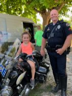 Do you have a license for that hog young lady? Officer Michael Pettee assists this little local.