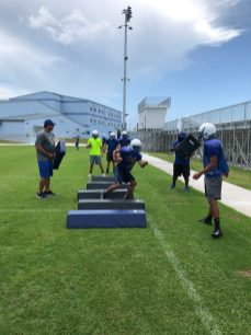 The football players occupy a new practice field behind the bleachers of the new complex.