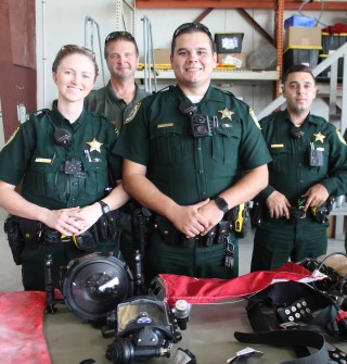 TOP COPS – National Night Out draws a crowd - A group of people standing around a motorcycle - Sheriff