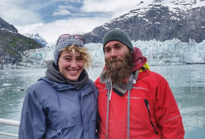 A man and Woman standing in front of a mountain in Alaska