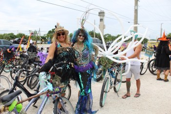 BROOMSTICK PARKING ONLY – Annual Witches' Ride raises funds for cancer research - A group of people standing next to a bicycle - Road bicycle
