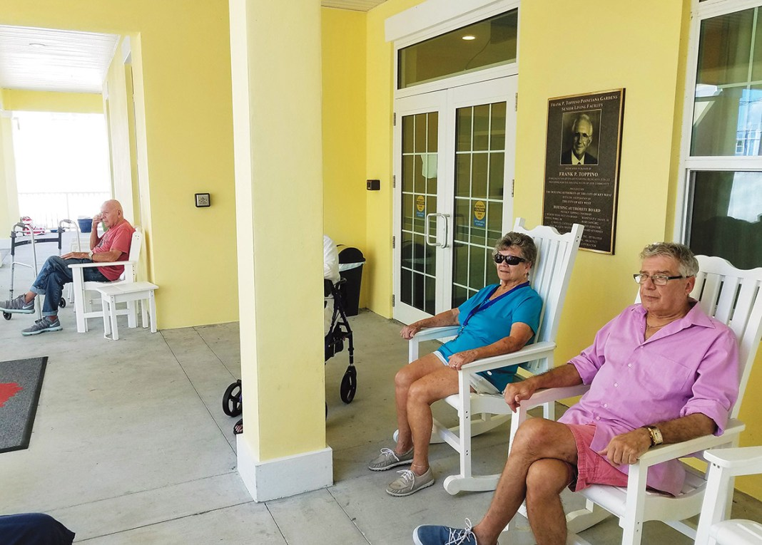 Rocking chairs line the front porch at Poinciana Gardens, where residents Barbara Jones, Joseph Canosa and others enjoy the shaded breeze and easy conversation.
