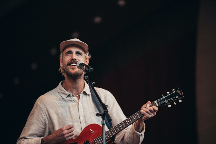 Strange American Dreamer – Rayland Baxter Returns for 3rd COAST Is Clear Festival - A man standing on a stage holding a guitar - Rayland Baxter
