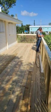 Guess what? Habitat is still helping homeowners recover from Irma - A person standing on top of a wooden building - Deck