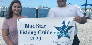 Add three more Blue Star Fishing Guides - A person holding a sign posing for the camera - T-shirt