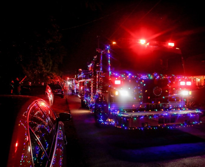 CLAUS, CAROLERS COME TO TOWN - A street filled with traffic at night - Fête