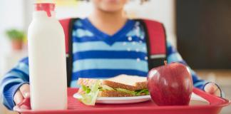 School lunch debts linger – Principal corrects superintendent's claims - A small child sitting on a table - Cafeteria