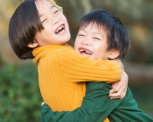 Little Asian boy and big sister hugging, laughing