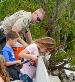 FWC Officer Welchhan gets a few tips from 7-year-old Wyatt Thompson and his sister Layla. Wyatt says he has been fishing for four years and caught lots of fish, including a shark.