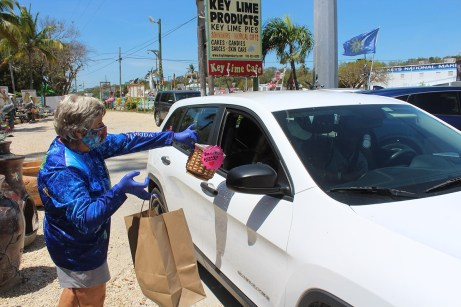 A motorist prepares to hand out a donation before retrieving their hot meal from a volunteer. Jim McCarthy/Keys Weekly